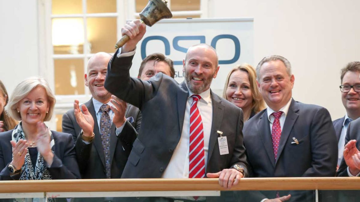 Richard Godfrey, CEO of BerGenBio, ringing the bell at the Oslo Stock Exchange. He is surounded by members of the BergenBio staff.
