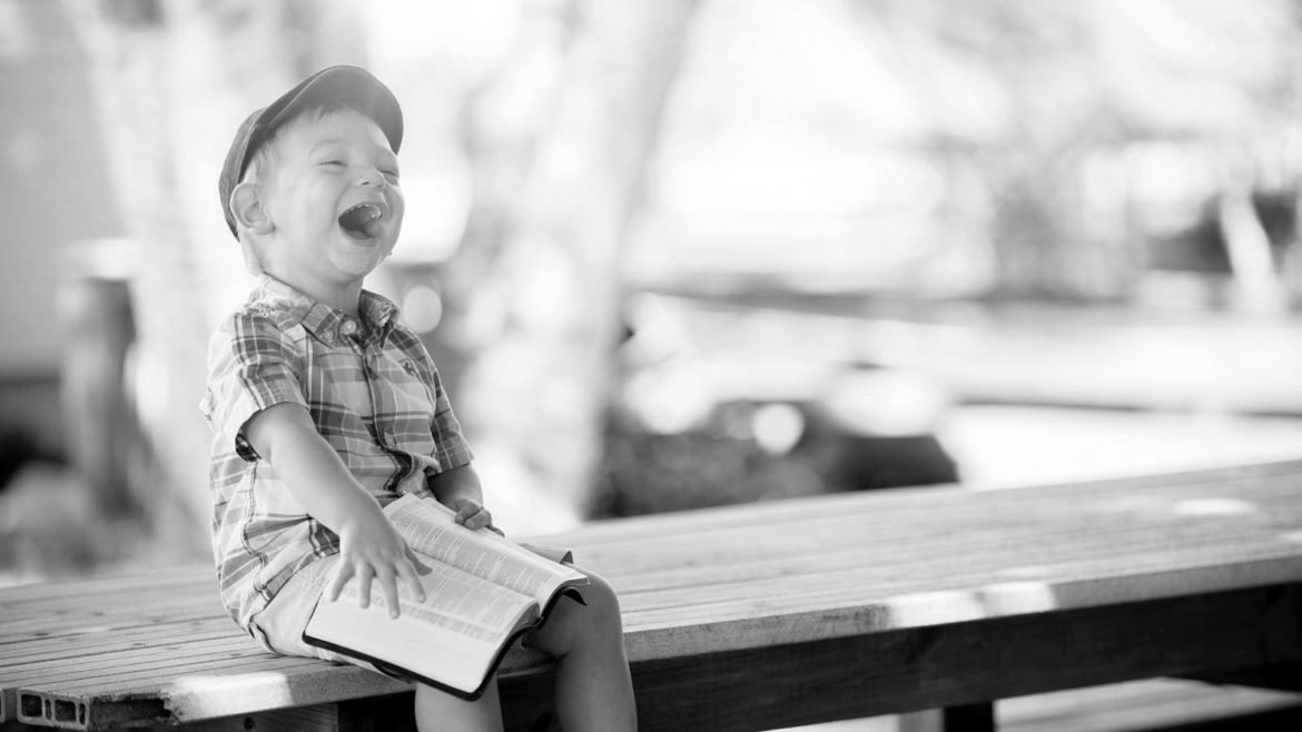 Young boy reading a book and laughing.